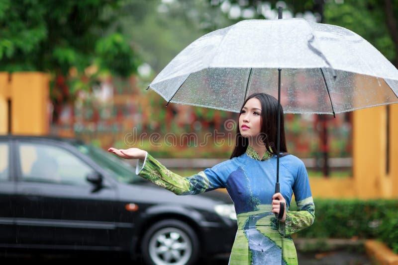 Vietnamesiskt paraply för Ao dai för kvinnakläder hållande i regnet royaltyfria foton