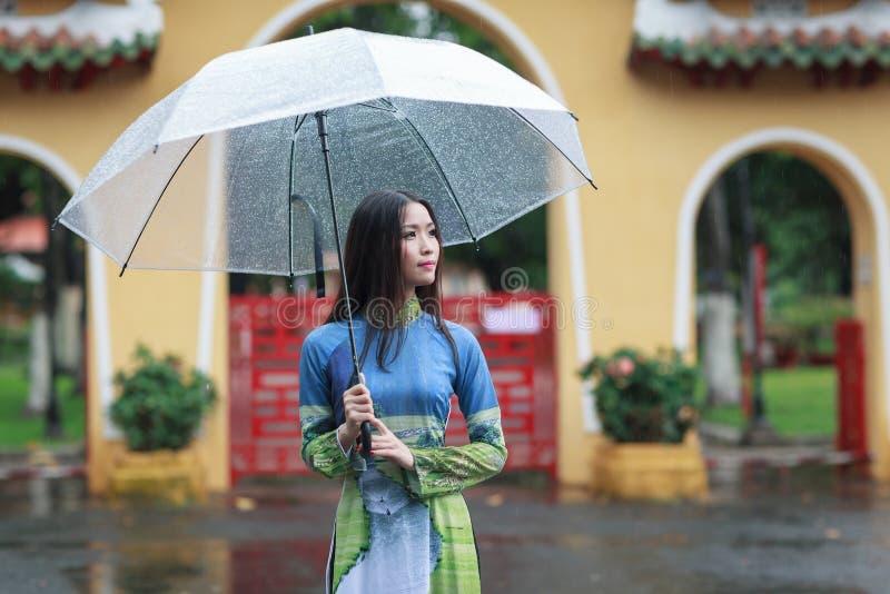 Vietnamesiskt paraply för Ao dai för kvinnakläder hållande i regnet fotografering för bildbyråer