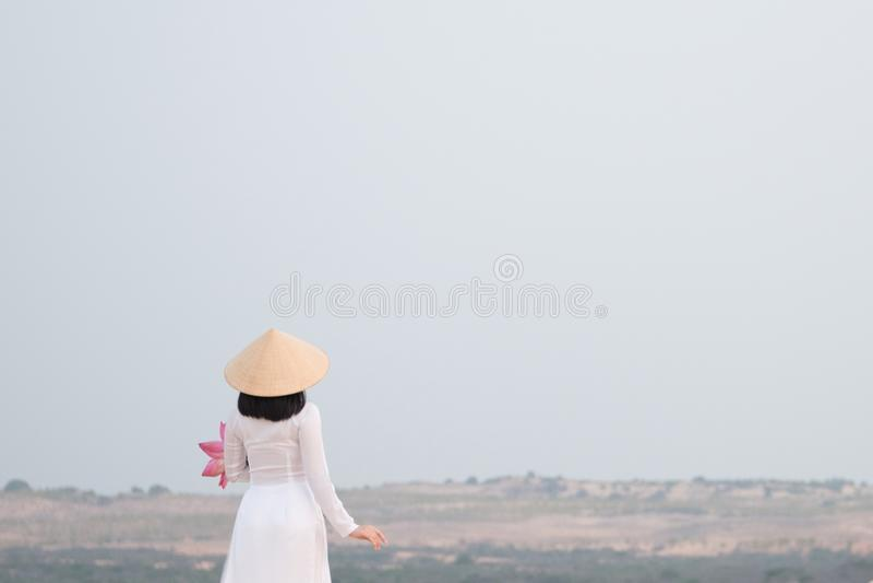 Vietnamita bonito que guarda Lotus cor-de-rosa na duna de areia branca foto de stock
