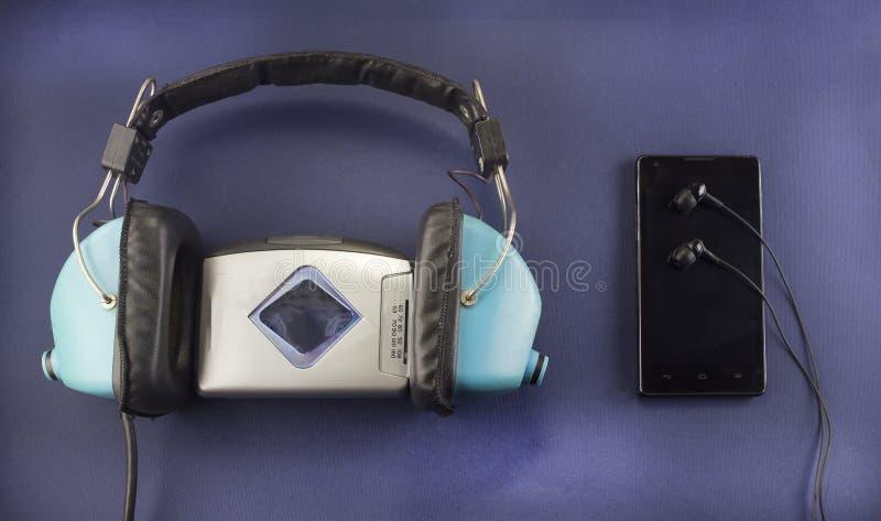 Vieux écouteurs et joueur audio, téléphone moderne avec des écouteurs, musique de fond bleue image libre de droits