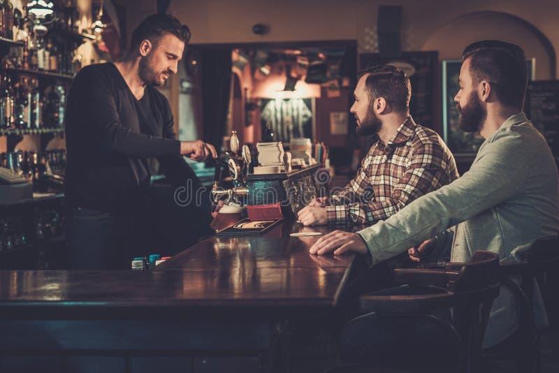 Vieux amis buvant de la bière pression au compteur de barre dans le bar photo stock
