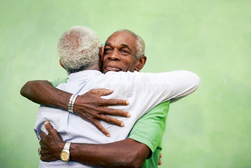 Vieux amis, deux hommes supérieurs d'afro-américain se réunissant et étreignant images stock