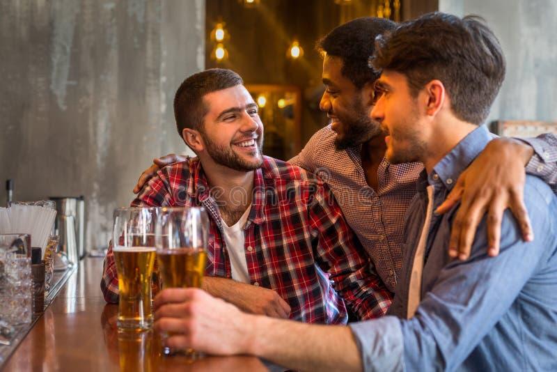 Vieux amis divers buvant de la bière pression dans le bar photos stock