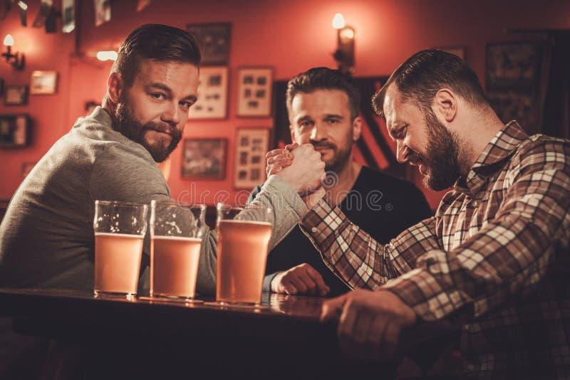 Vieux amis gais ayant le défi de bras de fer dans un bar photographie stock libre de droits