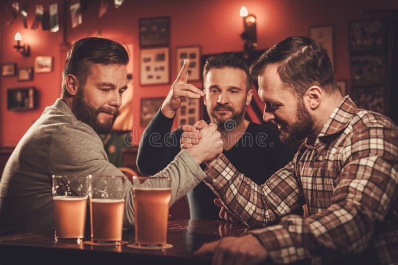 Vieux amis gais ayant le défi de bras de fer dans un bar image libre de droits