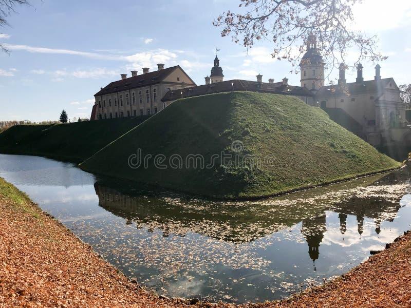 Vieux, antique château médiéval avec des spiers et des tours, murs de pierre et brique entourée par un fossé protecteur avec de l photo libre de droits