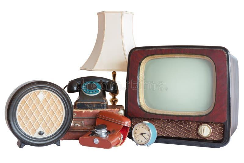 Vieux articles de ménage : TV, radio, appareil-photo, alarme, téléphone, lampe de table images libres de droits