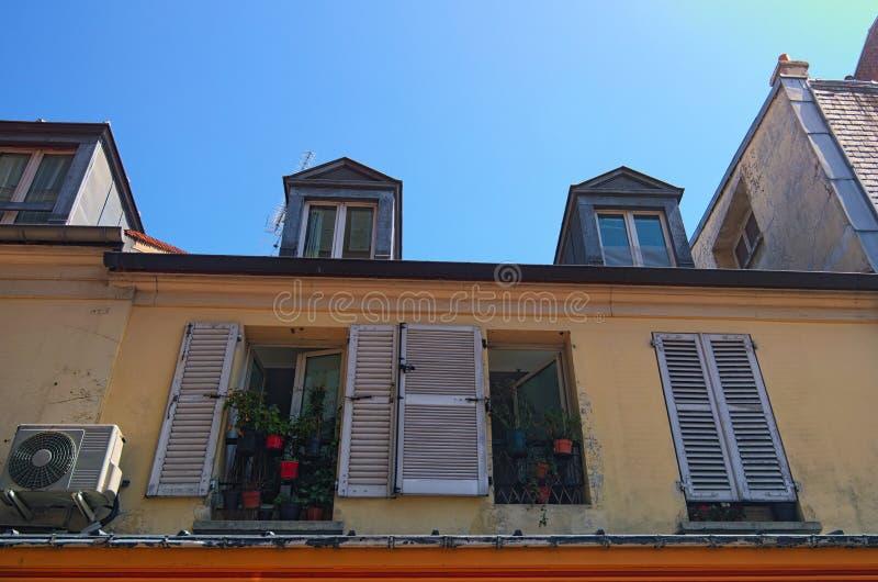 Vieux bâtiment dans la rue de Montmartre Windows avec beaucoup de fleurs dans des pots de fleurs Jour ensoleillé de source Paris, images libres de droits