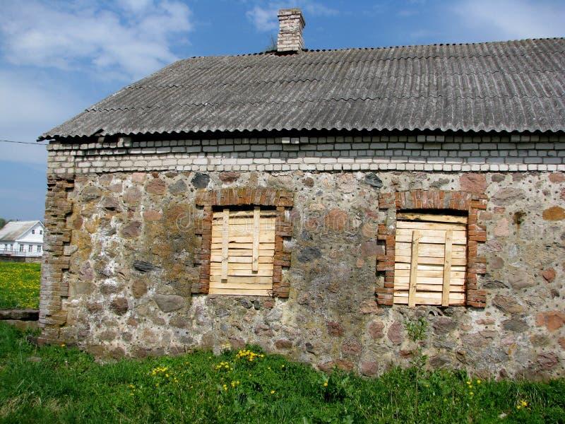 Vieux bâtiment de pierre de village avec embarqué vers le haut de deux fenêtres photographie stock