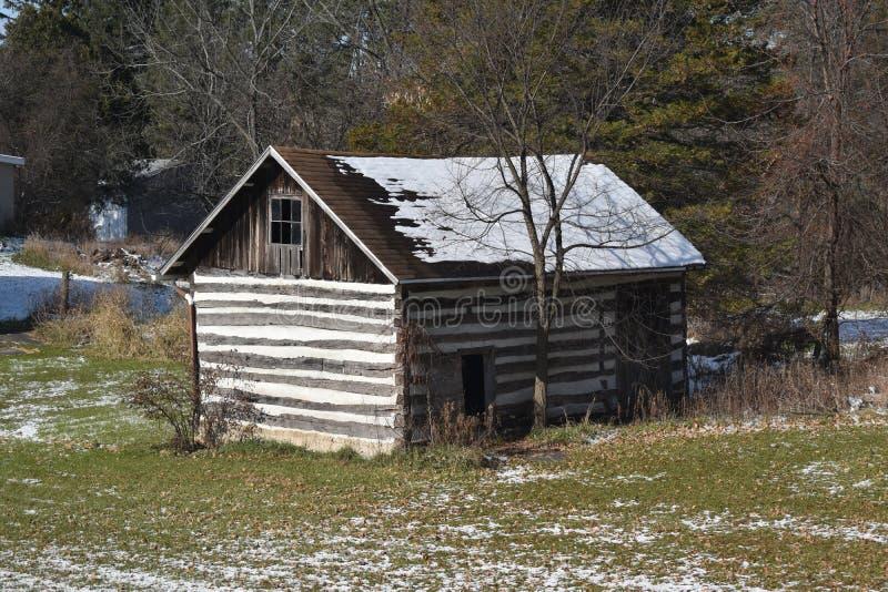 Vieux bâtiment de stockage de cabine de rondin dans les bois avec la neige légère en hiver photos stock