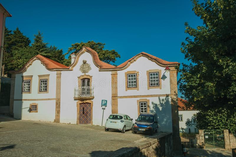 Vieux bâtiment et voitures garées devant peu de place à Guarda photographie stock