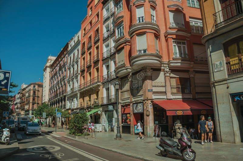 Vieux bâtiments avec des magasins et les gens sur une rue passante de Madrid image stock