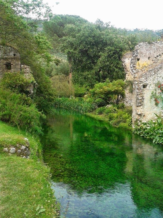 Vieux bâtiments de émiettage de pierre sur une petite rivière dans le jardin de la nymphe en Italie image libre de droits
