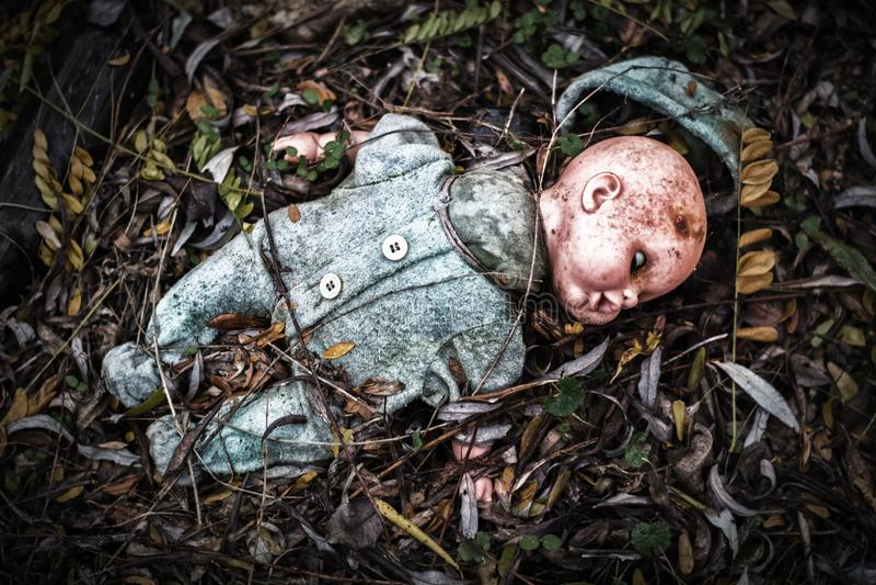 Vieux bébé cassé abandonné - la poupée se décompose dans la forêt effrayante images stock