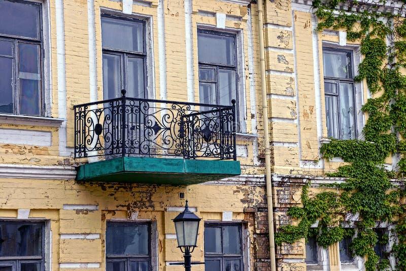 Vieux balcon ouvert sur la façade du bâtiment envahi avec des usines image stock