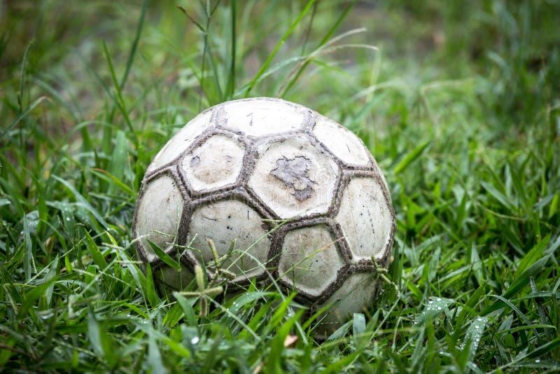 Vieux ballon de football dans l'herbe sur un pluvieux photo stock