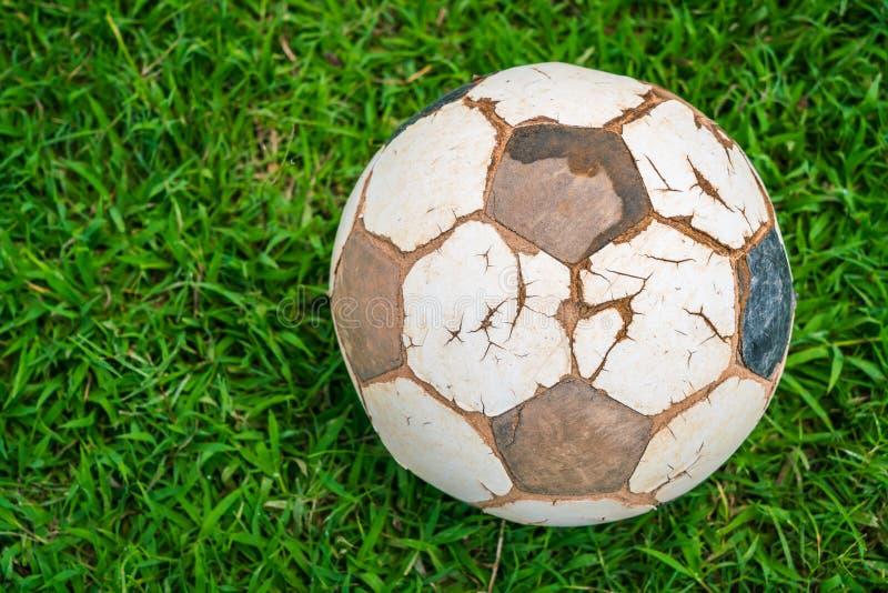 Vieux ballon de football sur l'herbe verte de ressort frais photo stock