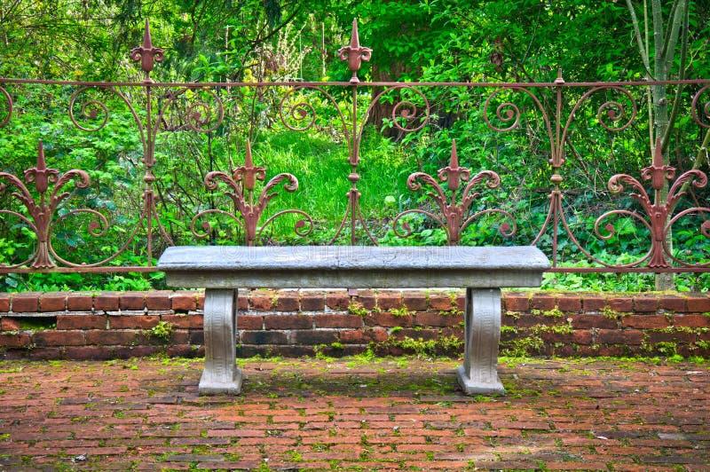 Vieux banc dans le jardin anglais formel avec la barrière fleurie de fer travaillé images stock