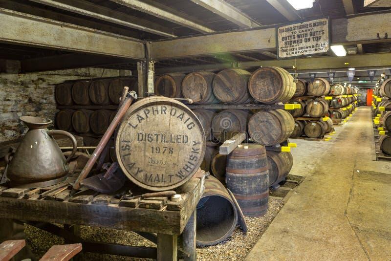 Vieux barils et tonneaux en bois de Lafroaig dans la cave à la distillerie de whiskey en Ecosse image libre de droits