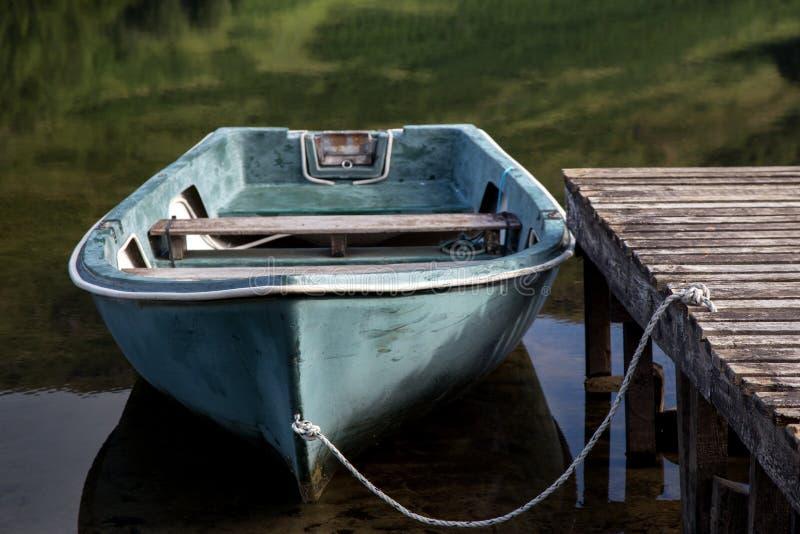 Vieux bateau à rames amarré à un loch des montagnes écossais photos stock