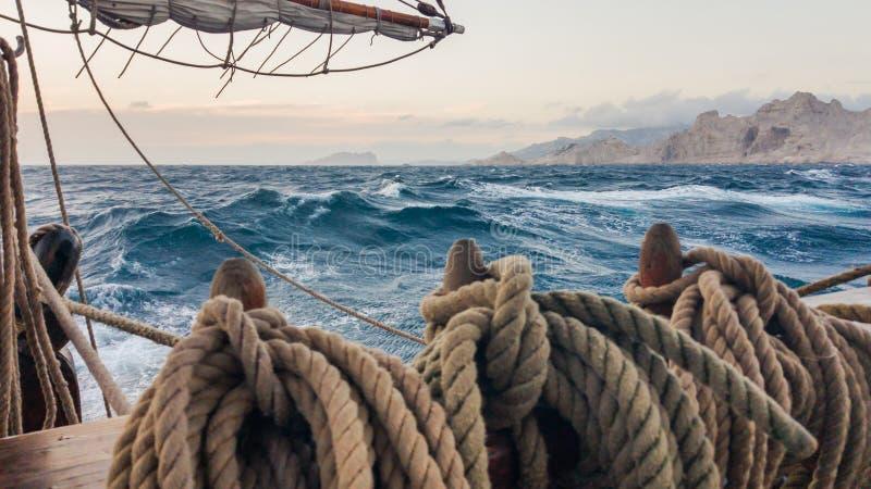 Vieux bateau de navigation fonctionnant sur la mer près des roches Goupille assiégeante sur laquelle les cordes photo stock