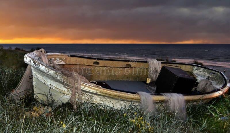 Vieux bateau de pêche au lever de soleil photo stock
