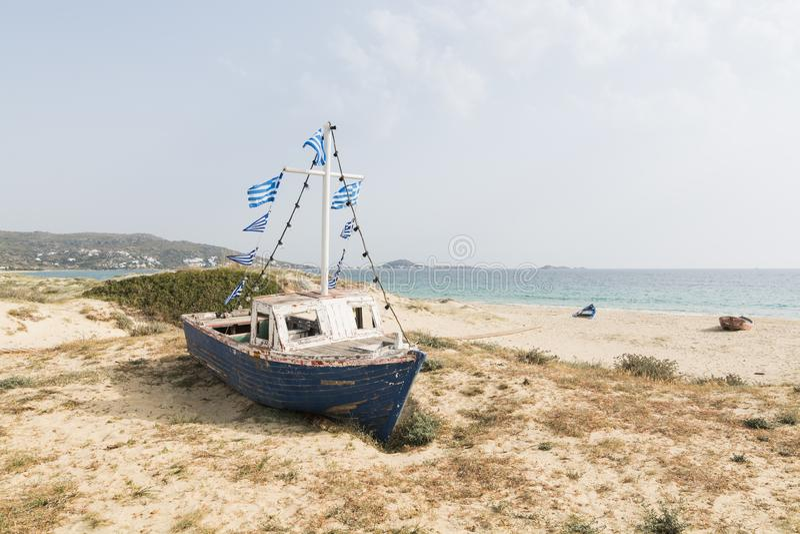 Vieux bateau de pêche en bois sur la plage avec les drapeaux grecs sur l'île de Naxos de mât, Grèce images stock