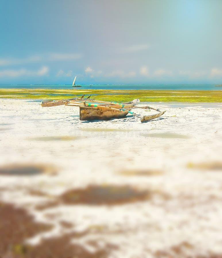 Vieux bateau de pêche sur la côte d'océan à marée basse Jour ensoleill? Zanzibar, Afrique photo libre de droits