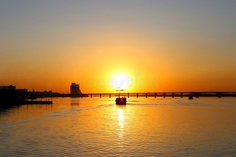 Vieux bateau de pirate de sailer, avec les voiles déchirées, au coucher du soleil photo stock
