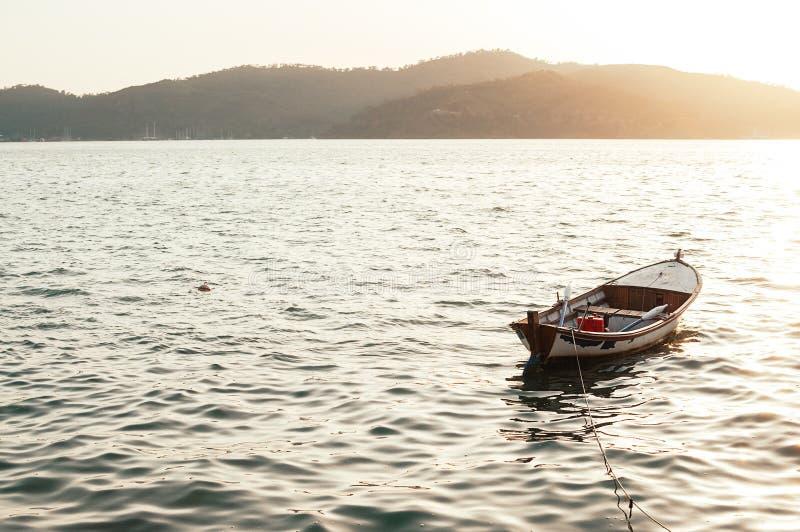 Vieux bateau de rangée en bois au coucher du soleil photos stock
