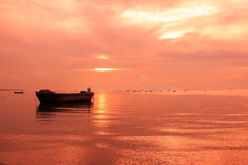 Vieux bateau devant le fond de coucher du soleil photo stock