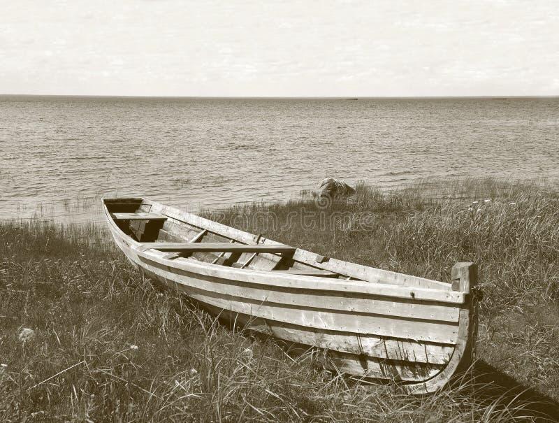 Vieux bateau en bois sur l'herbe près de la banque de lac photographie stock libre de droits