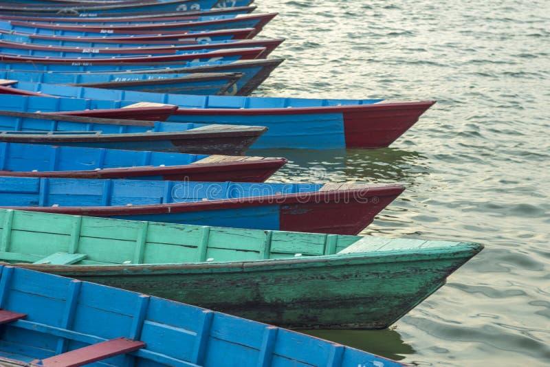 Vieux bateaux verts rouges bleus en bois vides sur le support de l'eau dans une rangée photos stock