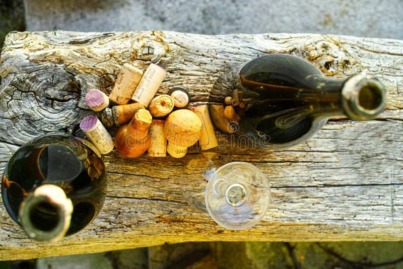Vieux bouchons de vigne et bouteilles utilisés de cidre sur le backdro texturisé en bois images stock