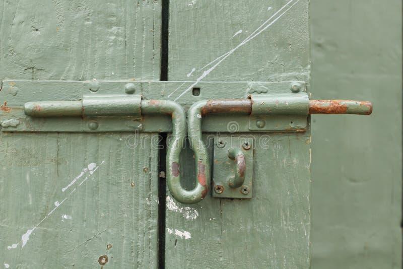 Vieux boulon de fer à la porte en bois verte photographie stock