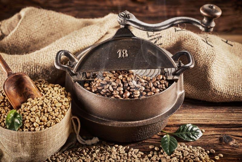 Vieux brûleur de café antique de fonte avec des haricots photographie stock