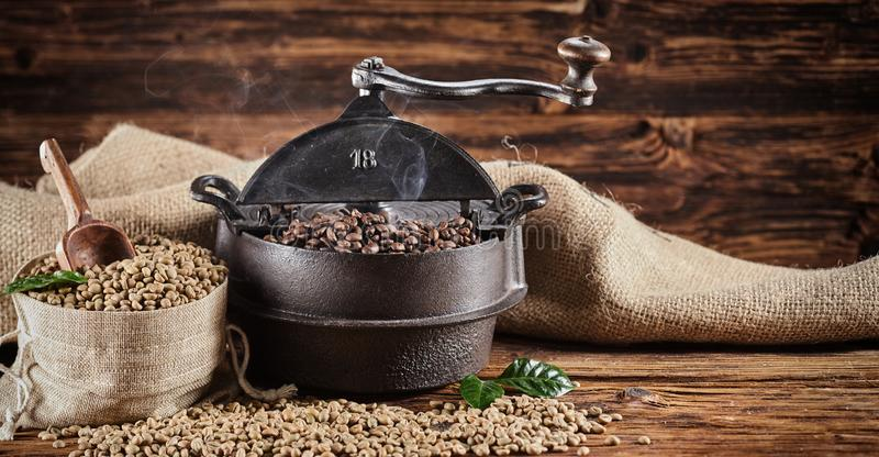 Vieux brûleur de café de fonte de cru et haricots crus images libres de droits