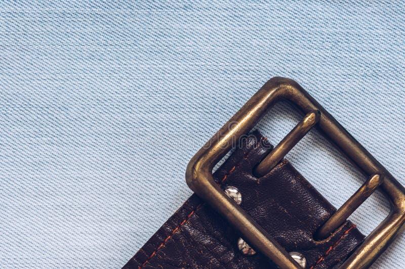 Vieux bracelet en cuir avec la boucle sur le fond de denim photos stock
