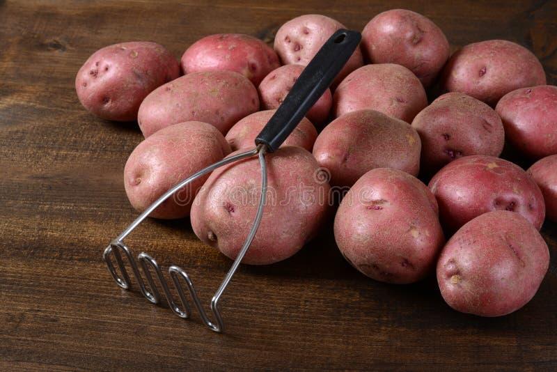 Vieux broyeur de pomme de terre avec les pommes de terre rouges image libre de droits