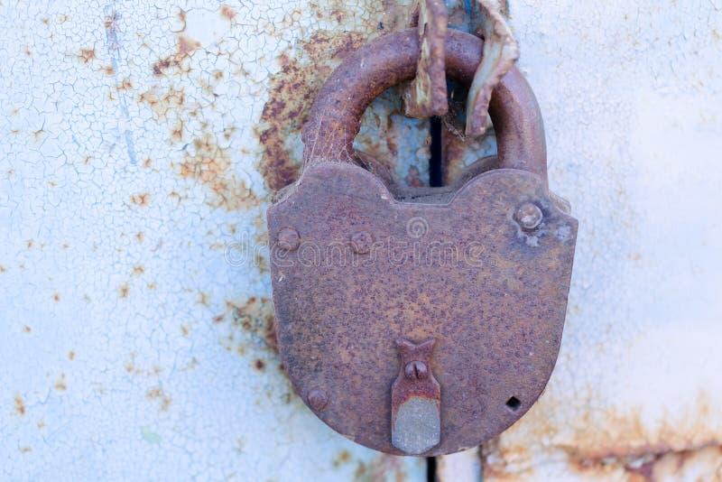 Vieux cadenas rouillé sur une porte en métal avec la peinture bleue criquée photo libre de droits