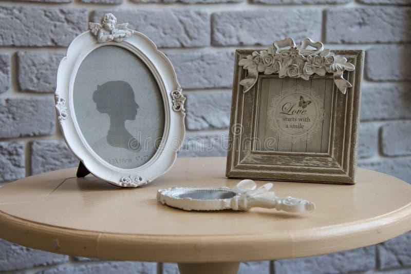 Vieux cadres de tableau, miroir menteur sur la table avec le fond gris de mur de briques, plan rapproché images libres de droits