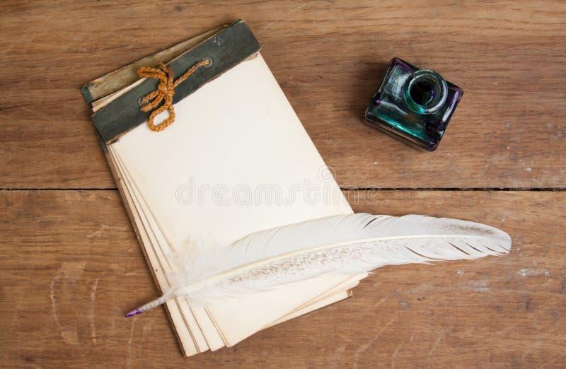 Vieux cahier, crayon lecteur d'encre de cannette et encrier encastré sur le Ba en bois image libre de droits