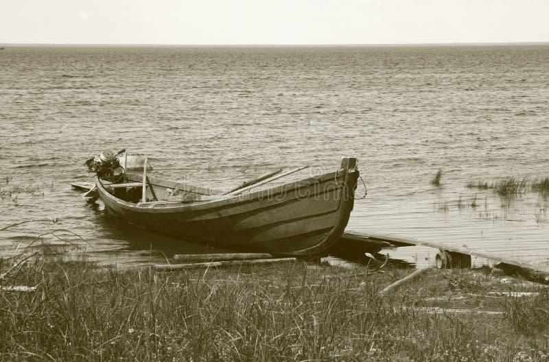 Vieux canot automobile de pêche en bois à la banque de lac photos stock