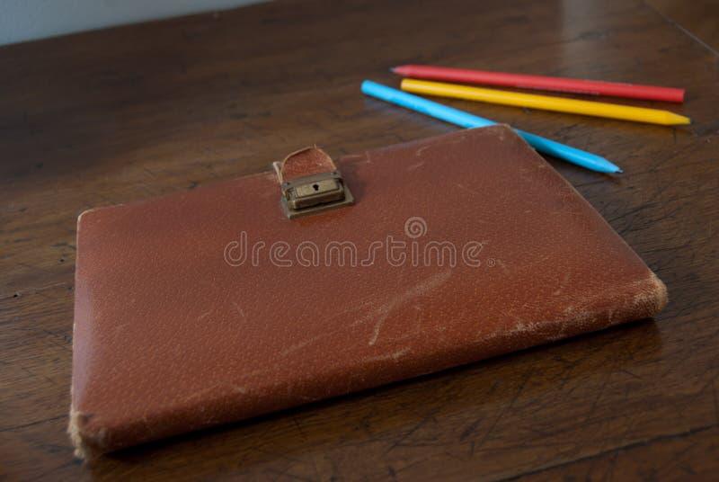 Vieux carnet avec la couverture en cuir sur une table en bois et des crayons colorés photographie stock libre de droits
