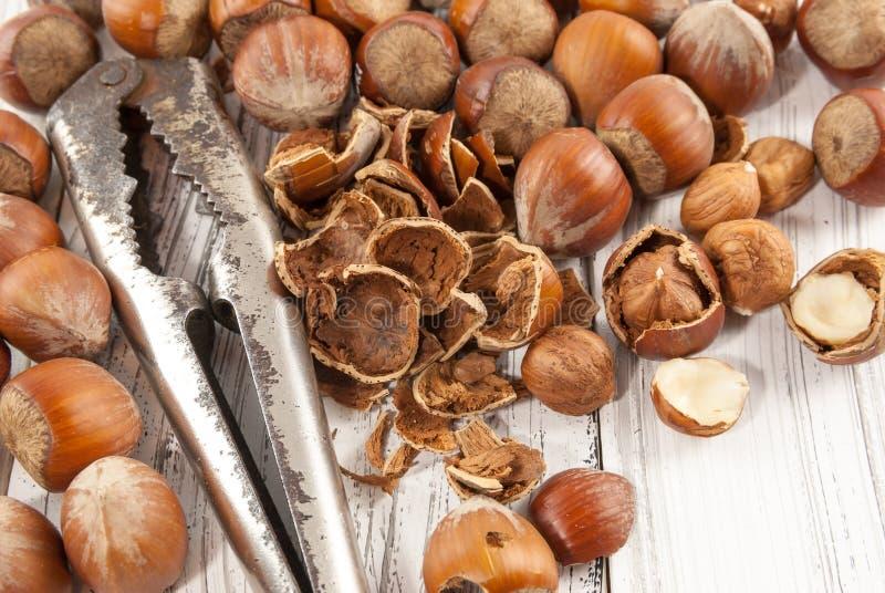 Vieux casse-noix et noisettes sur le fond en bois blanc photos stock