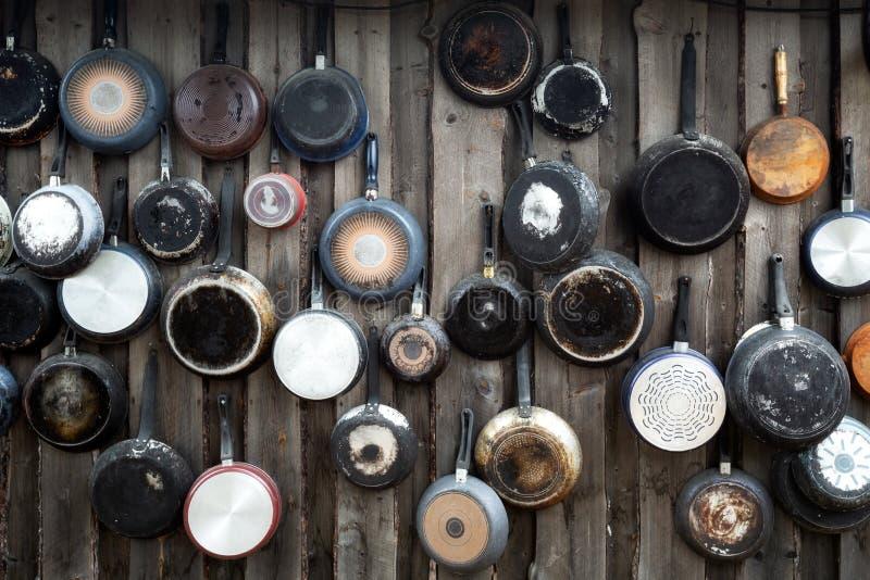 Vieux casseroles de cuisine accrochées au mur en bois Différentes tailles de casseroles au mur, Décoration maison, arrière-plan c photographie stock