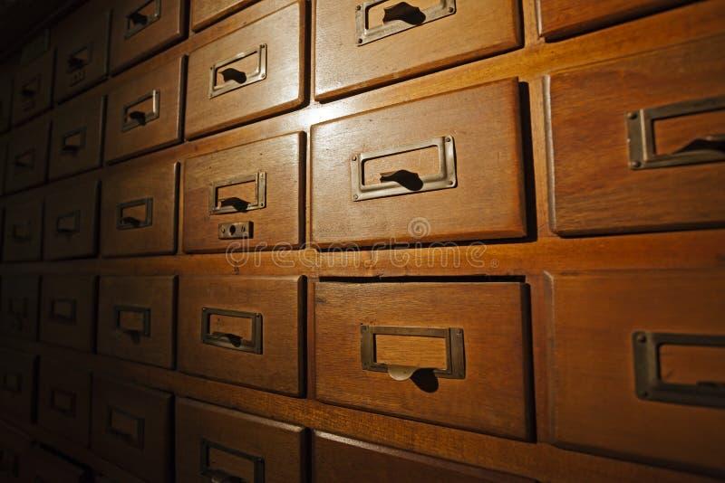Vieux catalogue sur fiches en bois, lumière de tache. images stock