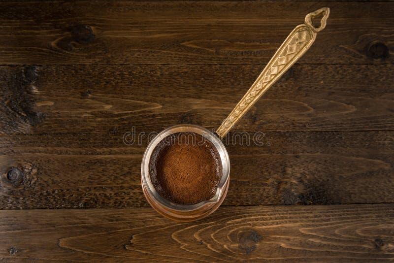Vieux cezve de cuivre de Brown avec du café Au-dessus de la table en bois brune comme fond photo libre de droits