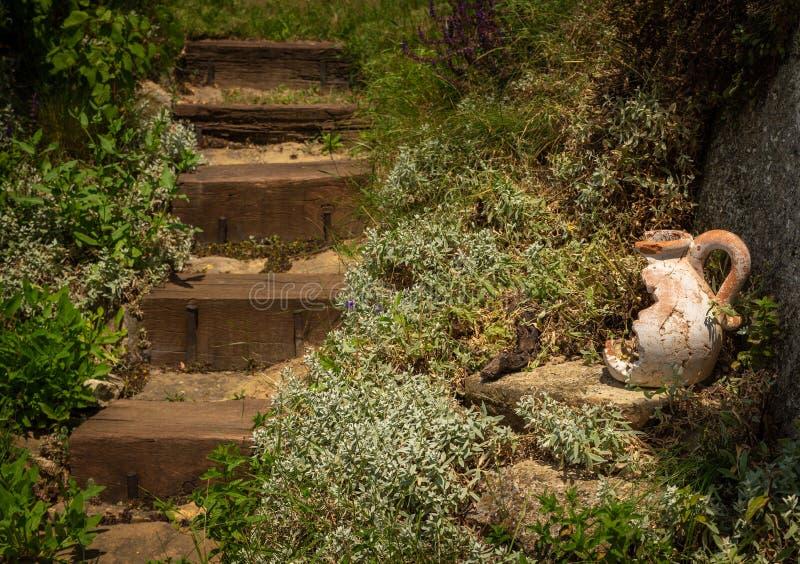 Vieux chandelier en céramique cassé près des étapes en bois rustiques dans le jardin d'été images libres de droits