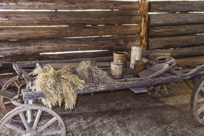 Vieux chariot en bois avec les oreilles sèches et les ustensiles en bois dedans d'une vieille grange image stock